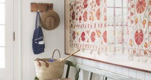 Oversized framed tapestry and a bench in entryway